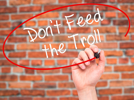 instigator: Man Hand writing Dont Feed the Troll with black marker on visual screen. Isolated on background. Business, technology, internet concept. Stock Photo