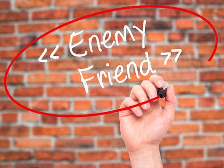 Man Hand writing Enemy - Friend with black marker on visual screen. Isolated on background. Business, technology, internet concept. Stock Photo Stock Photo - 53760691