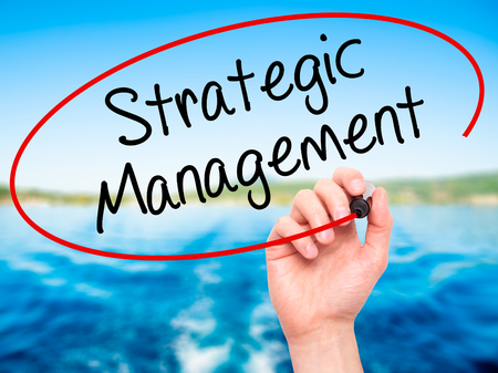 strategic focus: Man Hand writing Strategic Management with black marker on visual screen. Isolated on background. Business, technology, internet concept. Stock Photo Stock Photo