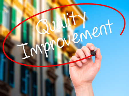 Man Hand writing Quality Improvement with black marker on visual screen. Isolated on background. Business, technology, internet concept. Stock Photo