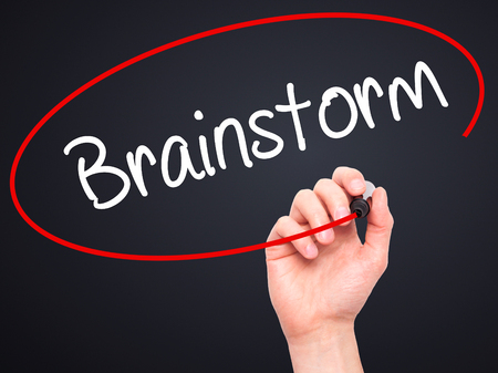consulting team: Man Hand writing Brainstorm with black marker on visual screen. Isolated on background. Business, technology, internet concept. Stock Photo