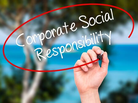 corporate social: Man Hand writing Corporate Social Responsibility with black marker on visual screen. Isolated on background. Business, technology, internet concept. Stock Photo Stock Photo