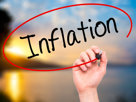 economic theory: Man Hand writing Inflation with black marker on visual screen. Isolated on background. Business, technology, internet concept. Stock Photo