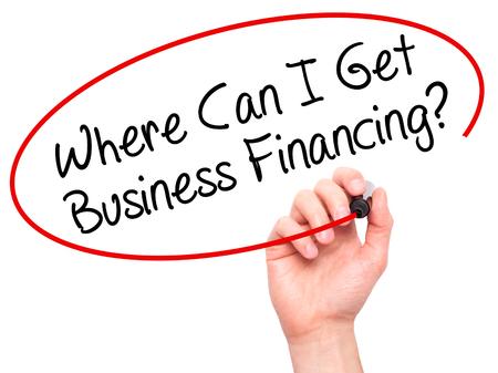 Escritura del hombre de la mano ¿Dónde puedo obtener financiación de las empresas? con marcador negro en la pantalla visual. Aislado en el fondo. Negocios, la tecnología, el concepto de internet. Foto de stock