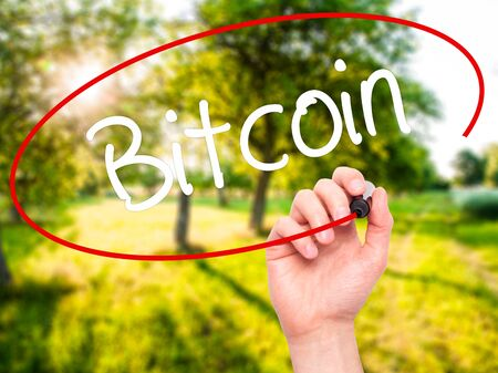Man Hand writing Bitcoin with black marker on visual screen. Isolated on background. Business, technology, internet concept. Stock Photo