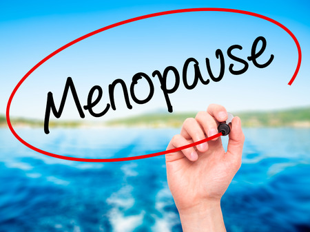 ovaries: Man Hand writing Menopause with black marker on visual screen. Isolated on background. Business, technology, internet concept. Stock Photo