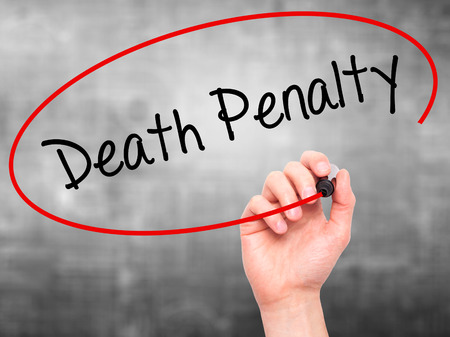 Man Hand writing Death Penalty with black marker on visual screen. Isolated on background. Business, technology, internet concept. Stock Photo