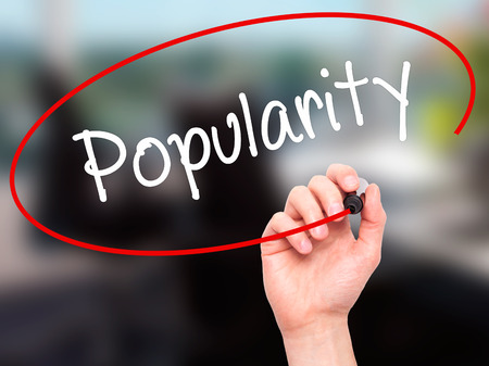popularity: Man Hand writing Popularity with black marker on visual screen. Isolated on background. Business, technology, internet concept. Stock Photo