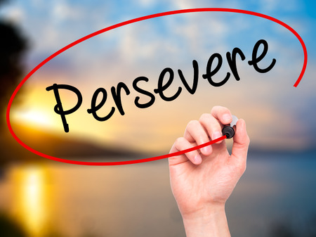 Man Hand writing Persevere with black marker on visual screen. Isolated on background. Business, technology, internet concept. Stock Photo