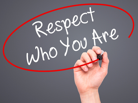 dignity: Man Hand writing Respect Who You Are with black marker on visual screen. Isolated on background. Business, technology, internet concept. Stock Photo