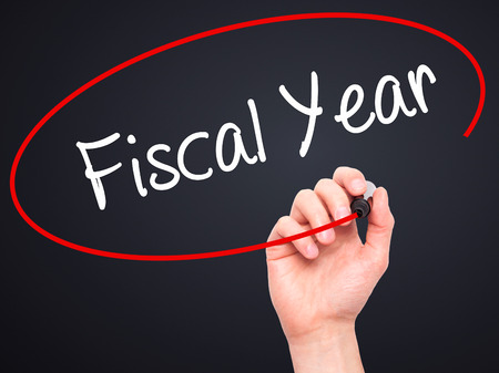 fiscal: Man Hand writing Fiscal Year with black marker on visual screen. Isolated on background. Business, technology, internet concept. Stock Photo