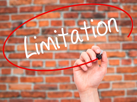 bounds: Man Hand writing Limitation with black marker on visual screen. Isolated on background. Business, technology, internet concept. Stock Photo