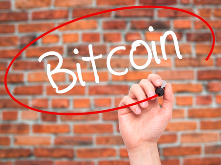 net trade: Man Hand writing Bitcoin with black marker on visual screen. Isolated on background. Business, technology, internet concept. Stock Photo