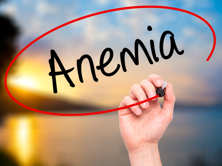 decreased: Man Hand writing Anemia  with black marker on visual screen. Isolated on background. Business, technology, internet concept. Stock Photo