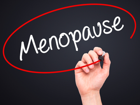 midlife: Man Hand writing Menopause with black marker on visual screen. Isolated on background. Business, technology, internet concept. Stock Photo