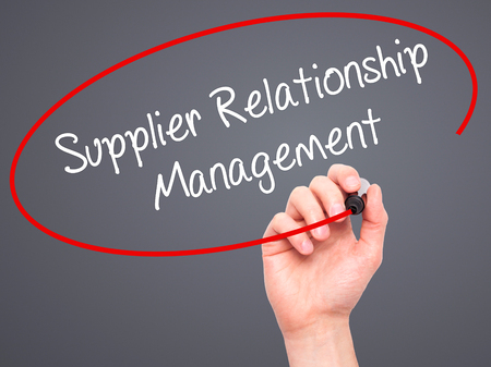 supplier: Man Hand writing Supplier Relationship Management with black marker on visual screen. Isolated on background. Business, technology, internet concept. Stock Photo
