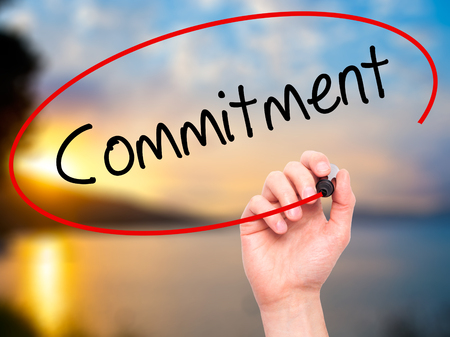 consign: Man Hand writing Commitment with black marker on visual screen. Isolated on background. Business, technology, internet concept. Stock Photo