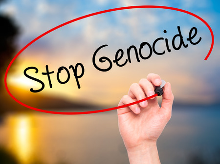 genocide: Man Hand writing Stop Genocide with black marker on visual screen. Isolated on background. Business, technology, internet concept. Stock Photo