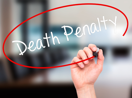 punitive: Man Hand writing Death Penalty with black marker on visual screen. Isolated on background. Business, technology, internet concept. Stock Photo
