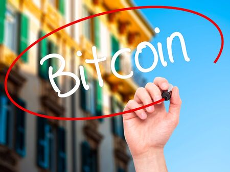 e cash: Man Hand writing Bitcoin with black marker on visual screen. Isolated on background. Business, technology, internet concept. Stock Photo