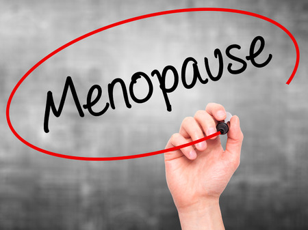 Man Hand writing Menopause with black marker on visual screen. Isolated on background. Business, technology, internet concept. Stock Photo