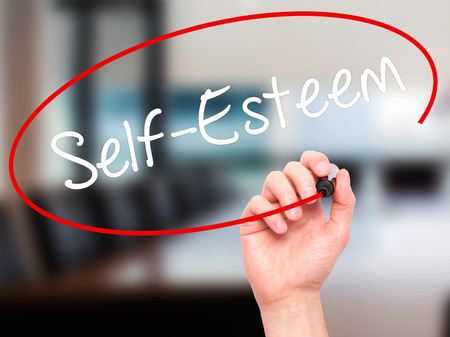 self worth: Man Hand writing Self-Esteem with white marker on visual screen. Isolated on background. Business, technology, internet concept. Stock Photo Stock Photo