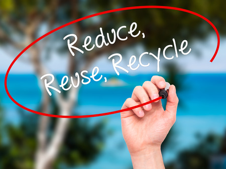 reduce reutiliza recicla: Man Hand writing Reduce Reuse Recycle with white marker on visual screen. Isolated on background. Business, technology, internet concept. Stock Photo Foto de archivo