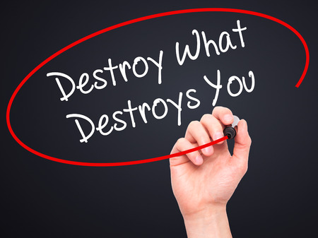 annihilate: Man Hand writing Destroy What Destroys You with white marker on visual screen. Isolated on background. Business, technology, internet concept. Stock Photo