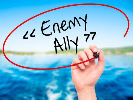 adversary: Man Hand writing Enemy - Ally with black marker on visual screen. Isolated on background. Business, technology, internet concept. Stock Photo