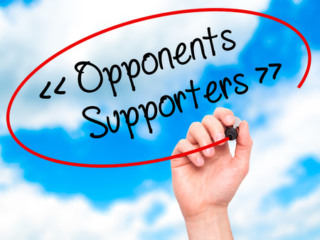 opponents: Man Hand writing Opponents - Supporters with black marker on visual screen. Isolated on background. Business, technology, internet concept. Stock Photo