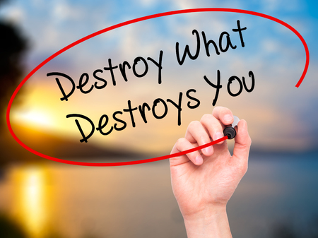 annihilate: Man Hand writing Destroy What Destroys You with black marker on visual screen. Isolated on background. Business, technology, internet concept. Stock Photo