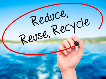 reduce reutiliza recicla: Man Hand writing Reduce Reuse Recycle with black marker on visual screen. Isolated on background. Business, technology, internet concept. Stock Photo