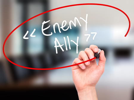 an ally: Man Hand writing Enemy - Ally with white marker on visual screen. Isolated on background. Business, technology, internet concept. Stock Photo Stock Photo