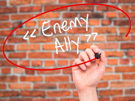 interdependence: Man Hand writing Enemy - Ally with white marker on visual screen. Isolated on background. Business, technology, internet concept. Stock Photo Stock Photo