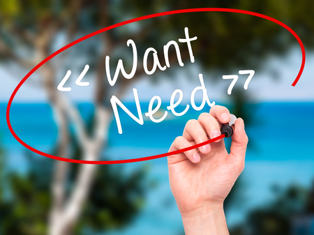 wish desire: Man Hand writing Want - Need  with white marker on visual screen. Isolated on background. Business, technology, internet concept. Stock Photo