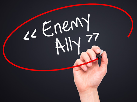 enemy: Man Hand writing Enemy - Ally with white marker on visual screen. Isolated on background. Business, technology, internet concept. Stock Photo Stock Photo