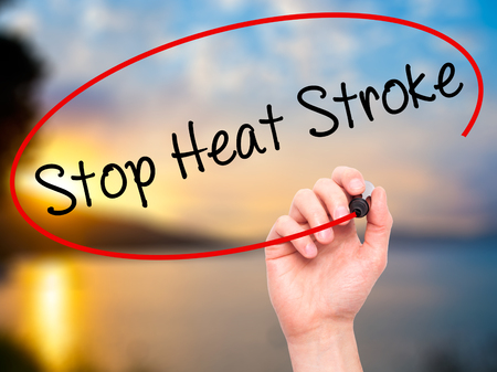 sunstroke: Man Hand writing Stop Heat Stroke with black marker on visual screen. Isolated on background. Business, technology, internet concept. Stock Photo