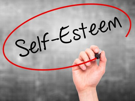 self worth: Man Hand writing Self-Esteem with black marker on visual screen. Isolated on background. Business, technology, internet concept. Stock Photo