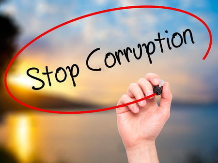 Man Hand writing Stop Corruption with black marker on visual screen. Isolated on background. Business, technology, internet concept. Stock Photo
