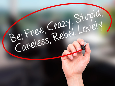 careless: Man Hand writing Be: Free, Crazy, Stupid, Careless, Rebel, Lovely with white marker on visual screen. Isolated on background. Business, technology, internet concept. Stock Photo Stock Photo