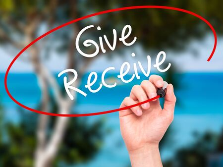 benevolence: Man Hand writing Give Receive with white marker on visual screen. Isolated on background. Business, technology, internet concept. Stock Photo