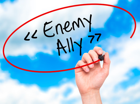oppose: Man Hand writing Enemy - Ally with black marker on visual screen. Isolated on background. Business, technology, internet concept. Stock Photo