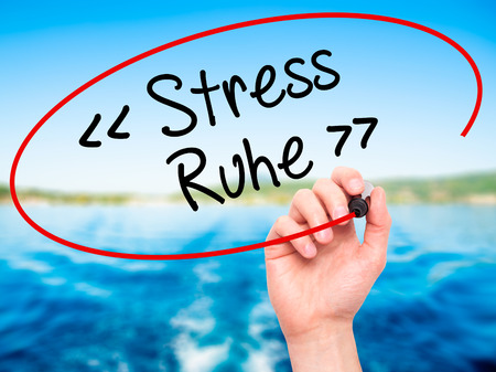 sense of security: Man Hand writing Stress Ruhe  (Stress - Peace in German) with black marker on visual screen. Isolated on background. Business, technology, internet concept. Stock Photo