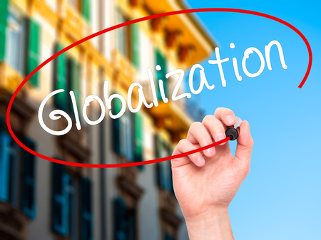 exportation: Man Hand writing Globalization with white marker on visual screen. Isolated on background. Business, technology, internet concept. Stock Photo