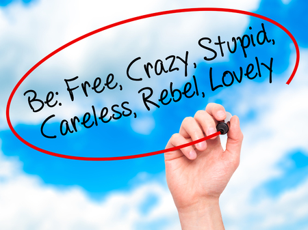 careless: Man Hand writing Be: Free, Crazy, Stupid, Careless, Rebel, Lovely with black marker on visual screen. Isolated on background. Business, technology, internet concept. Stock Photo