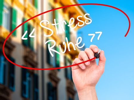 sense of security: Man Hand writing Stress Ruhe  (Stress - Peacein German) with white marker on visual screen. Isolated on background. Stock Photo