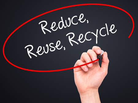 reduce reutiliza recicla: Man Hand writing Reduce Reuse Recycle with white marker on visual screen. Isolated on background.
