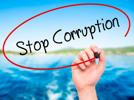 immoral: Man Hand writing Stop Corruption with black marker on visual screen. Isolated on background.