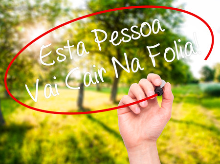 Man Hand writing Esta Pessoa Vai Cair Na Folia! (This Person Will be at Carnaval in Portuguese) with white marker on visual screen. Isolated on background. Business, technology, internet concept. Stock Photo