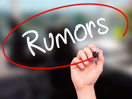 rumors: Man Hand writing Rumors with white marker on visual screen. Isolated on background. Stock Photo